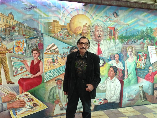 Artist Manuel Varrona standing before his mural in Tijuana