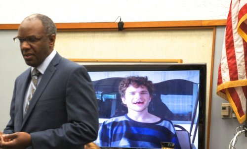 Defense attorney Michael Washington next to a photo of autistic man, Jamey.  Photo Weatherston.