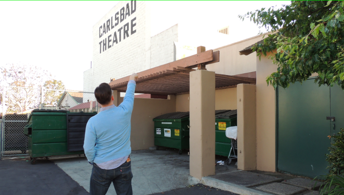 Clay Littrell points out dumpsters that trespassers use to climb onto the roof