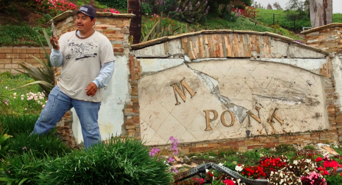 Humberto Caudillo, a landscape contractor, picks up brass letters from the sign that was damaged during a solo-vehicle crash just east of Pacific Rim Elementary School.
