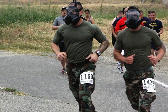 Camp Pendleton, April 13 - Sargent Artur Shvartsberg, left, and Corporal Stephen Johnson, right, run a half marathon, while wearing boots, utilities and gas masks.