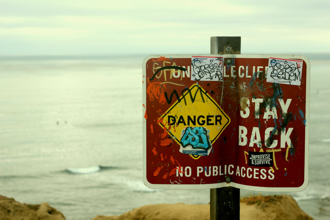 Dilapidated warning sign giving heed to potential cliff jumpers in Ocean Beach.