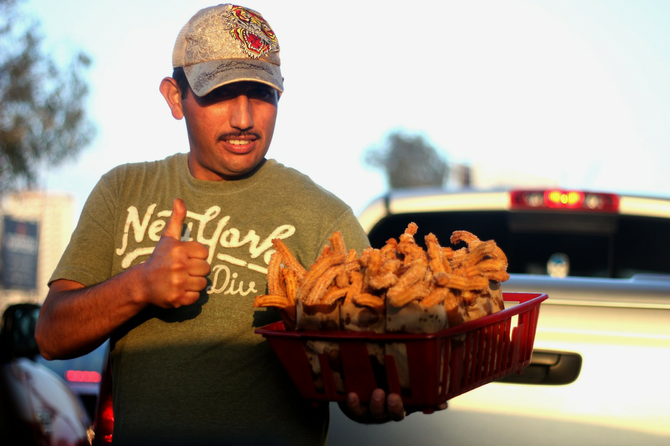 Churro salesman on the Tijuana border takes a break from sales to give a thumbs-up for the camera.