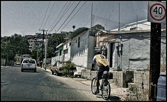 Neighborhood Photos TIJUANA,BAJA CALIFORNIA Cyclist along Juan Ojeda Avenue on Mineral de Santa Fe section of Tijuana/Ciclista en Avenida Juan Ojeda en Colonia Mineral de Santa Fe en Tijuana.
