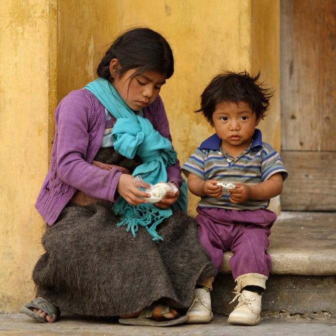 Street children enjoying a snack on the steps of the cathedral in San Cristobal de las Casas, Mexico.