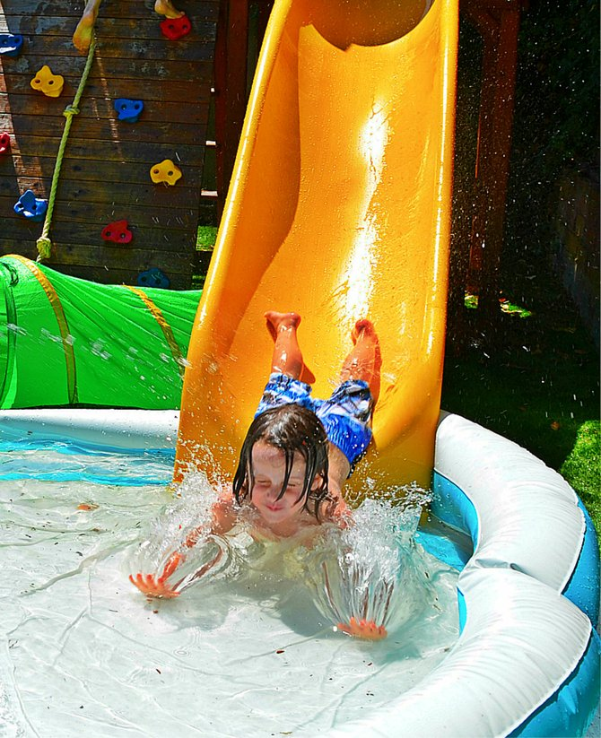 My son Fin, doing a belly slide at our back yard water park in Colleg Grove