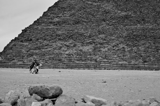 Men walking in front of a pyramid in Giza, Egypt