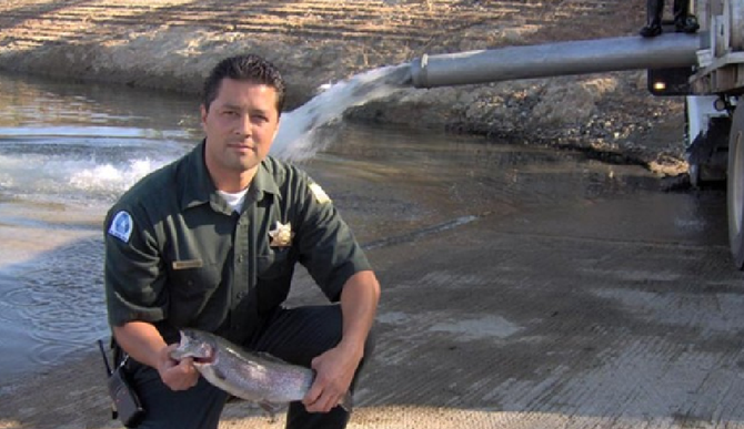 A ranger displays a trout while the lake is restocked (from lakejennings.org)