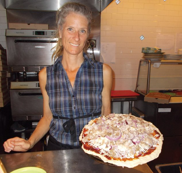 """It's the 'New Zealand,'"" says Sarah of the pizza she's just made. It's 14 inches, piled high with cheeses, chunks of meat, red onions."