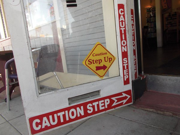 No less than four signs warn customers about  the step up into the bar.