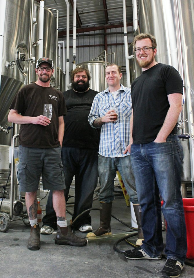 From left-to-right: Modern Times brewers Matt Walsh, Derek Freese, and Alex Tweet pose in front of their cellar with owner Jacob McKean.