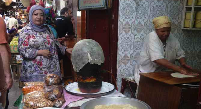 Vendors making pastilla in Fes's bustling medina.