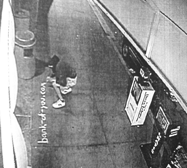 Security camera footage shows Olson chalking  anti–Bank of America messages on the sidewalk.
