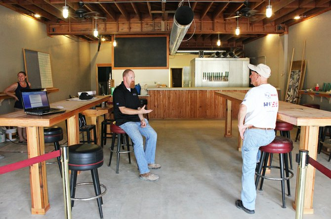 Owner and head brew Chuck McLaughlin tells an interested passerby what he can expect when FBC opens