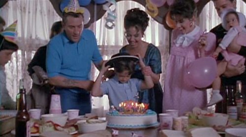 Leo blows out the birthday candles while DeNiro looks on.