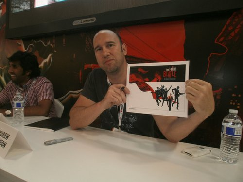 Fifth Beatle artist Andrew Robinson displays the free mini poster. Photo by Bart Mendoza