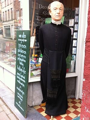 A stern wax-figure priest greets decadence-seeking shoppers.