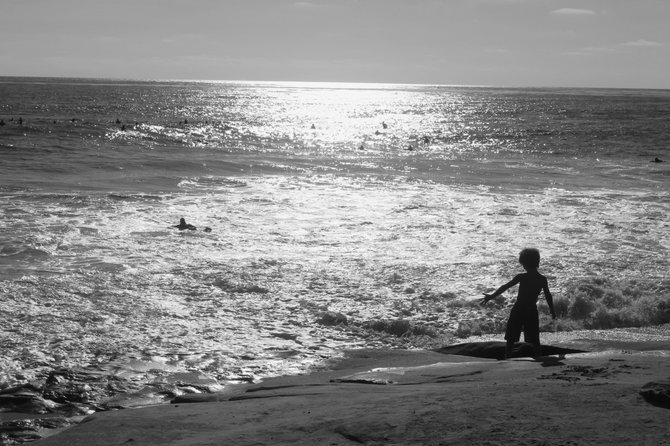 A young San Diego boy enjoying the waves on the shores of La Jolla.
