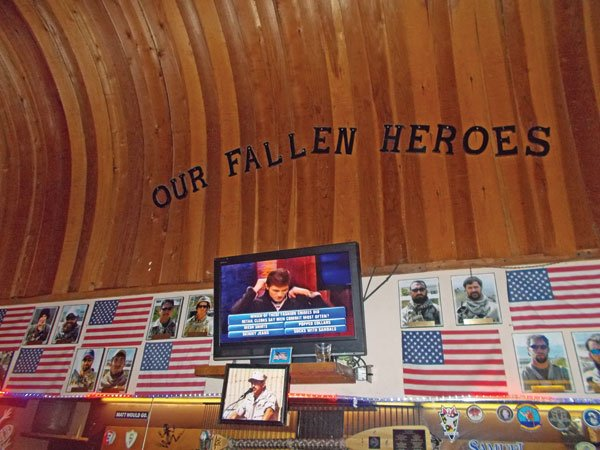 A photo of Chris Kyle, who was killed in February by a troubled ex-Marine, hangs in McP's shrine to fallen heroes.