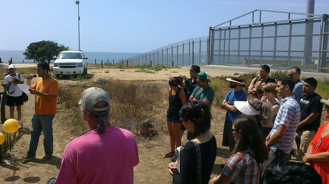Dan Watman, with unplugged microphone and Border Patrol watching closely from behind.