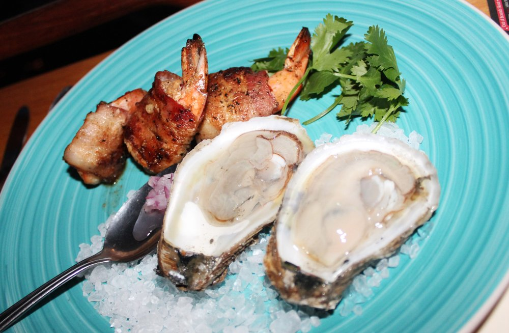 Bahia Falsa oysters served on the half-shell with three bacon-wrapped shrimp.