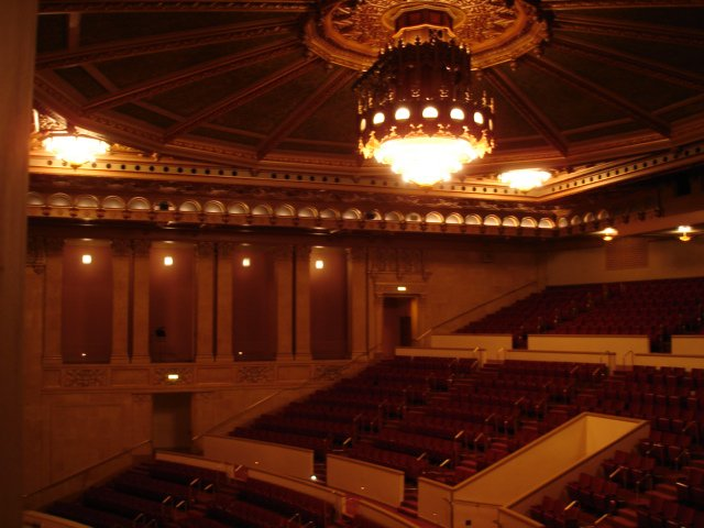 """As described in 1929, """"Hanging from the large gold dome of the auditorium is a huge electric fixture, studded with small lamps to imitate pearls, behind which are a number of small reflectors which throw a variation of colored lights on the ceiling of the dome."""" Credit www.akustiks.com."""