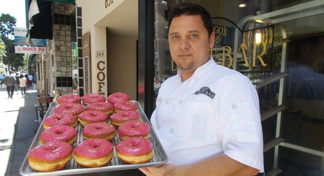 Santiago Campa outside the shop with a tray of raspberry-pistachio donuts