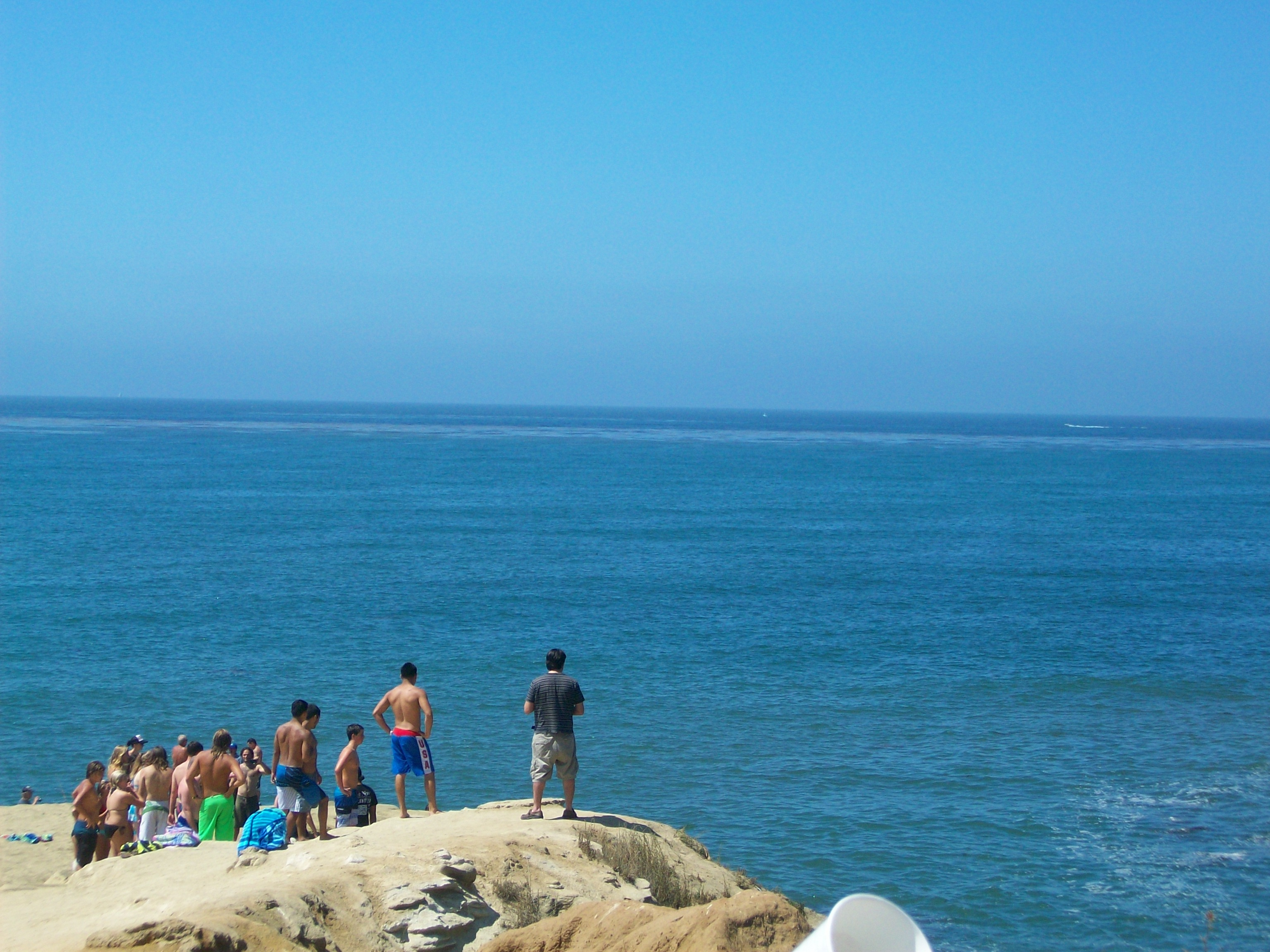 "Brave souls waiting to jump off Sunset Cliffs ""The Arch"" in Ocean Beach."