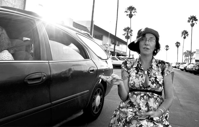 "this woman was standing outside of Cheswick's in OB. She was watching me take shots of my chair yesterday, and I asked her if she wanted to pose for me. She said ""Totally! This will be epic! You don't even know how epic this will be!"" ah, but I did know. I didn't catch her name because she was deep into her spirits and slurring a little bit. But she was able and willing and if I had hired her could not have been more perfect. she told me how she was from seattle and was on her way to Milwaukee to live with her sister. then she told me how epic this was. and she dragged on her cigarette and seemed unfazed by the traffic nearly grazing both sides of her. she got in my face and told me I was a golden goddess.
