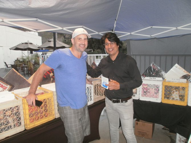 Record dealer and former M-Theory owner Eric Howarth, here with former Dragons frontman, Mario Escovedo, did brisk business at his vinyl booth. Photo by Bart Mendoza.