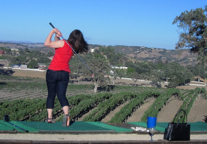 Golfer hits some balls into the winery at Veris Winery in Paso Robles.