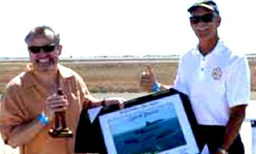 Scott Forney (left), senior VP at General Atomics Electromagnetic Systems, bags trophy for platinum air show sponsorship
