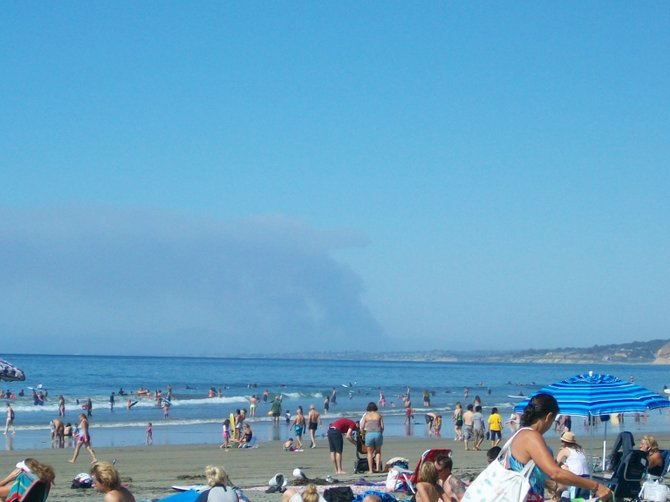 Smoke from a Camp Pendleton fire in the background of La Jolla Shores beach on a hot day.