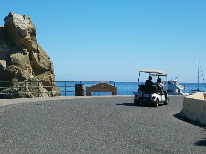 Golf carts drive along Pebbly Beach Road on Catalina Island.