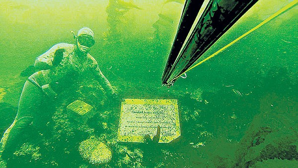 Volker Hoehne cleans off one of the markers at Tombstones, an unofffical underwater memorial park off the coast of La Jolla.