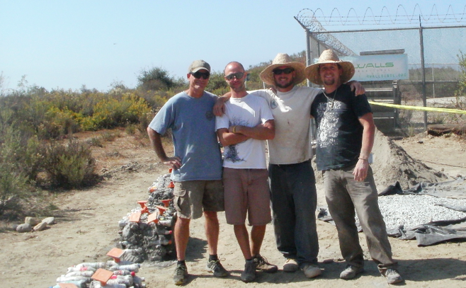 Two volunteers stand with Waylon Matson and Steven Wright (3rd and 4th from left) of 4 Walls International. Soda-bottle-filled bench bases on the left.