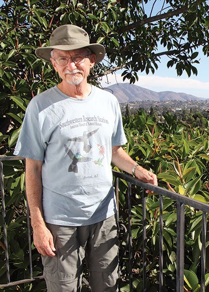 Ed Henry on his La Mesa balcony, next to a rubber tree frequented by red-masked and mitred parakeets