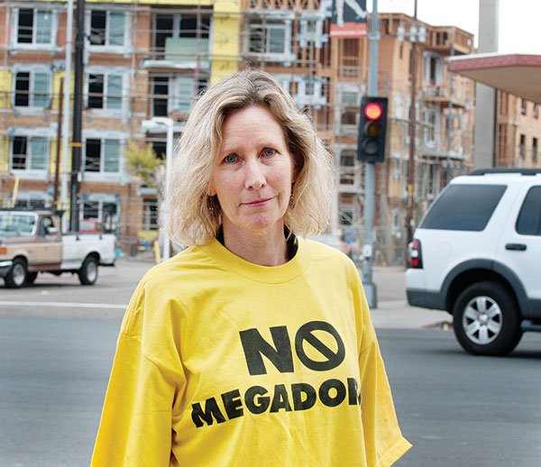 """No Megadorms,"" reads the T-shirt on Rolando resident Karen Collins, who warns, ""This single development will add 50 percent to Rolando's population."""