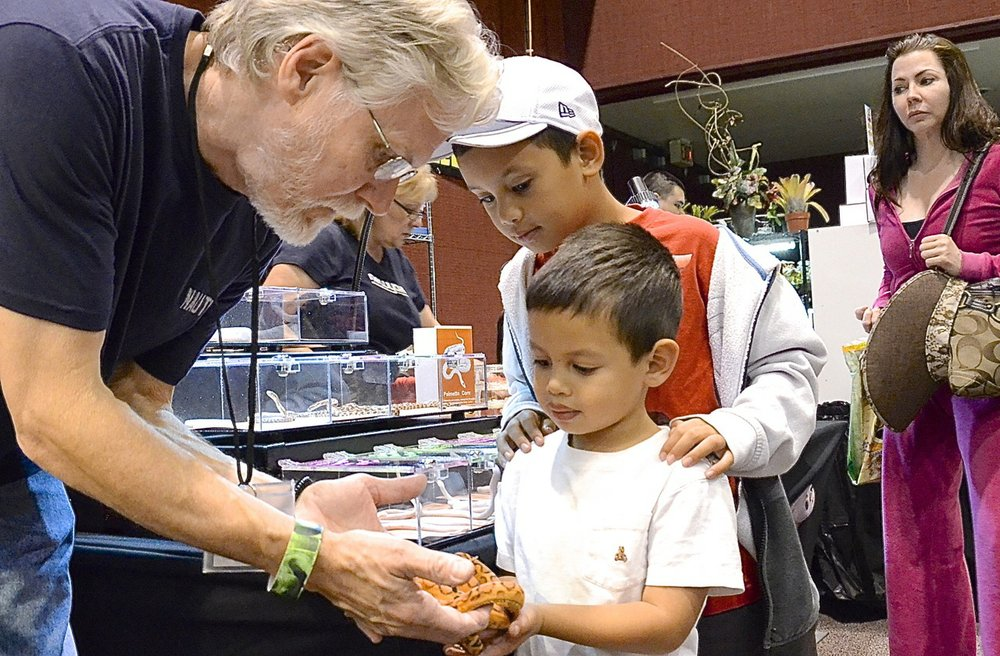 Exhibitor Don Soderberg kindly allowed two boys to touch his rare, mutant snake with no scales.