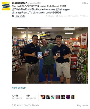Two Blockbuster employees pose with the chain's last customer.