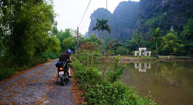 Small road in between majestic mountains on the way to Cuc Phuong National Park.