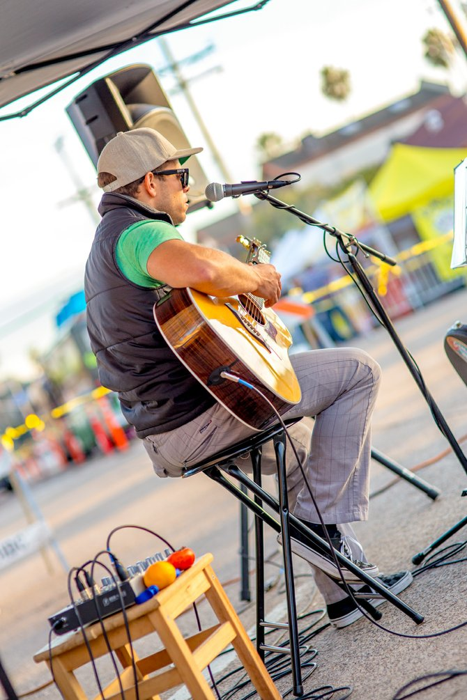 Local musician Andy Mauser provides a soundtrack to the Pacific Beach Farmers' Market.  Notice the fresh produce sitting on his amp.