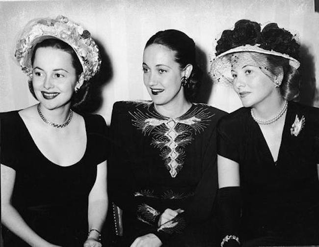 Olivia and Joan separated by Road warrior Dotty Lamour.