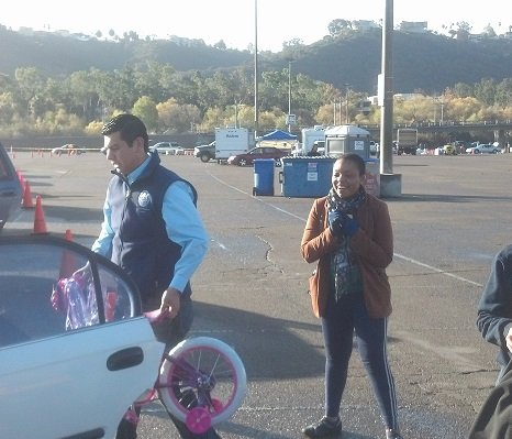 Mayoral hopeful David Alvarez loads a bike into a gift recipient's car