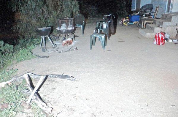 Sledgehammer in bottom left of evidence photo, barbecue scene.