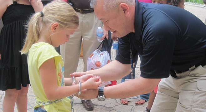 A U.S. Marshals official shows a girl how restraining cuffs work. Local defense attorneys aren't happy that all of their clients must wear them in federal court.