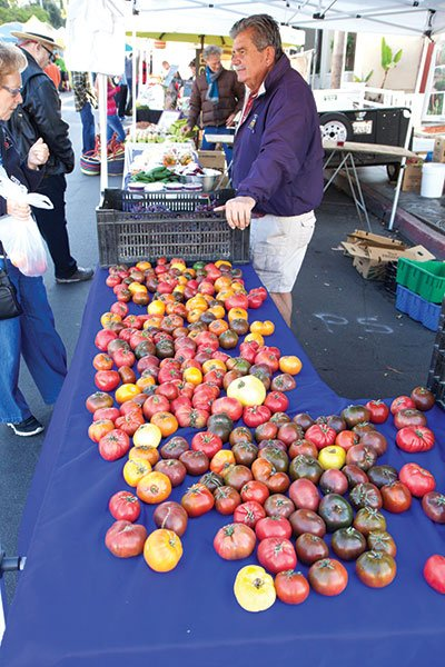 Organic tomatoes await purchase at the Tom King Farms stand at Little Italy's farmers' market.