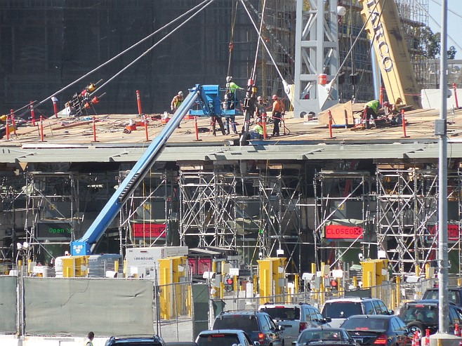 Construction crew assembles light towers with tension struts to support columns