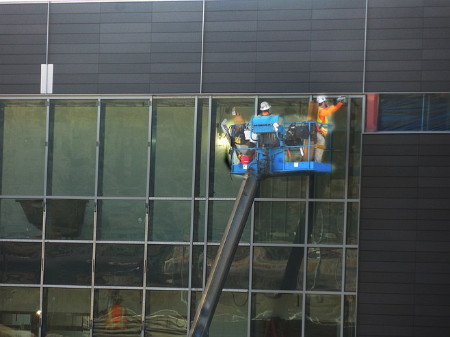 Men on a crane installing windows