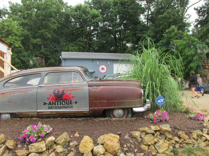 An old car serves as a storefront sign.